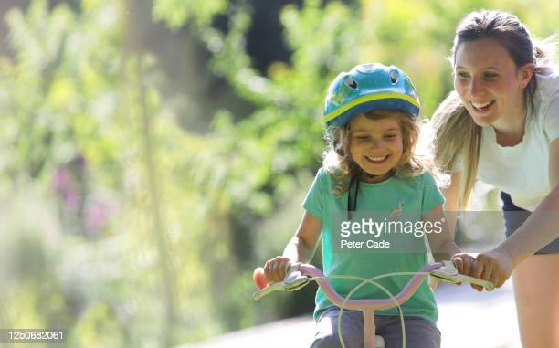 mother teaching daughter to ride a bike - daughter stock pictures, royalty-free photos & images
