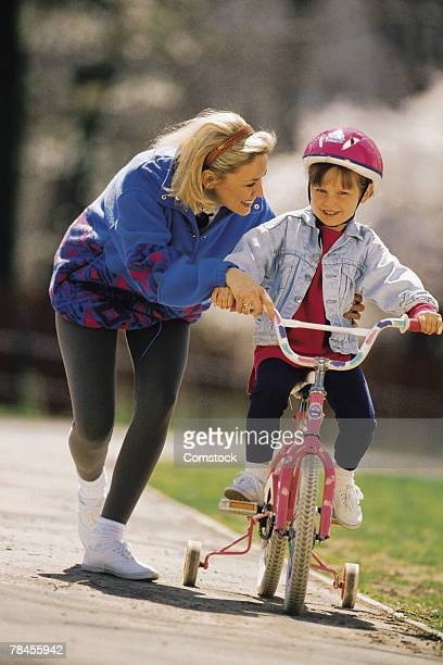 Mother teaching daughter to ride bicycle