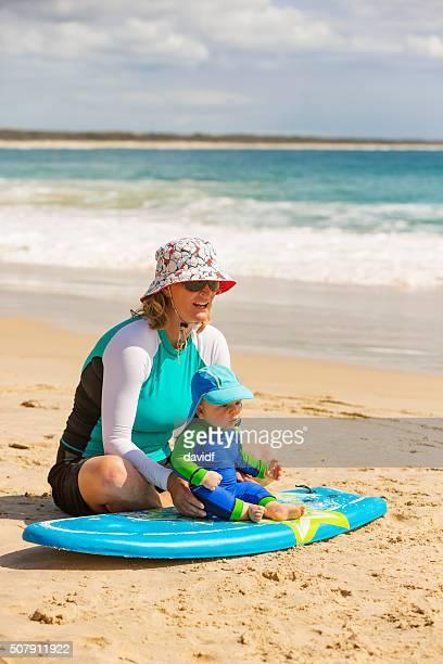 mother teaching her baby boy to surf - lange mouwen stockfoto's en -beelden
