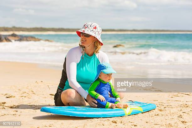 mother teaching her baby boy to surf - long sleeved stock photos and pictures