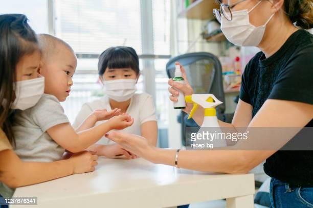 お母さんが子供たちに手をきちんと洗う方法を教える - 予防 ストックフォトと画像