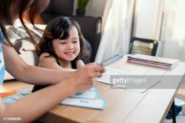 mother teaching her daughter at home - east asian ethnicity stock pictures, royalty-free photos & images