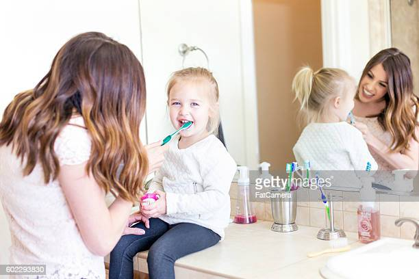 Mother teaching her daughter how to brush her teeth