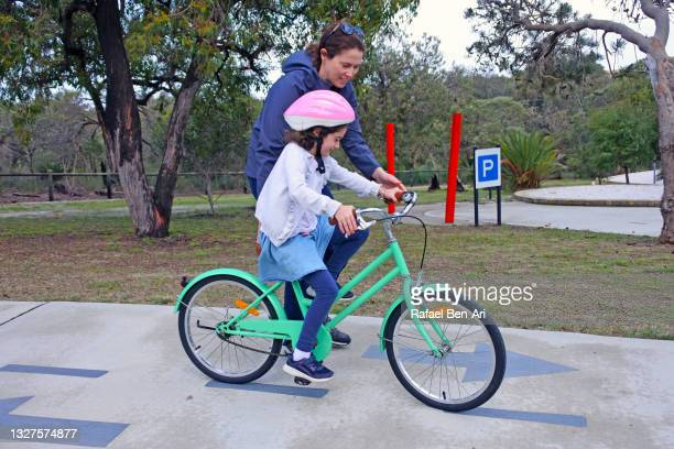 mother teaching her daughter to ride on a bicycle - rafael ben ari photos et images de collection