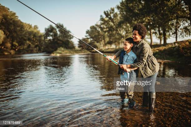 mother teaching her son how to catch a fish - fishing stock pictures, royalty-free photos & images