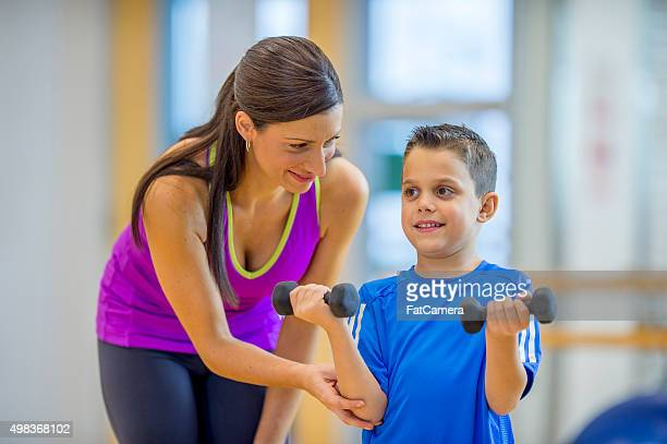 Mother Teaching Her Son How to Lift Weights