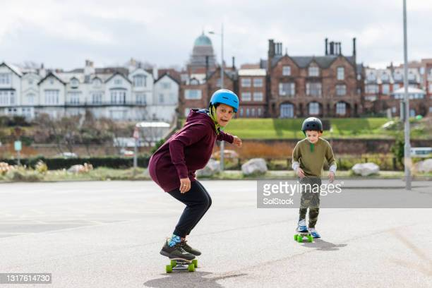mother teaching her son to skate - menopossibilities stock pictures, royalty-free photos & images
