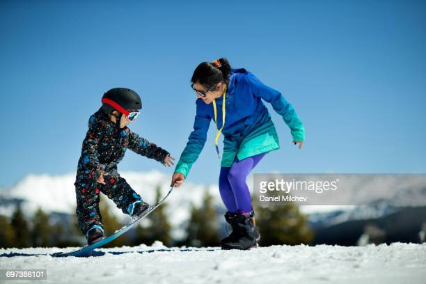 Mother teaching her young son how to snowboard.