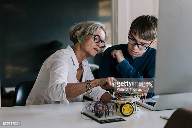 Mother teaching son about electronic
