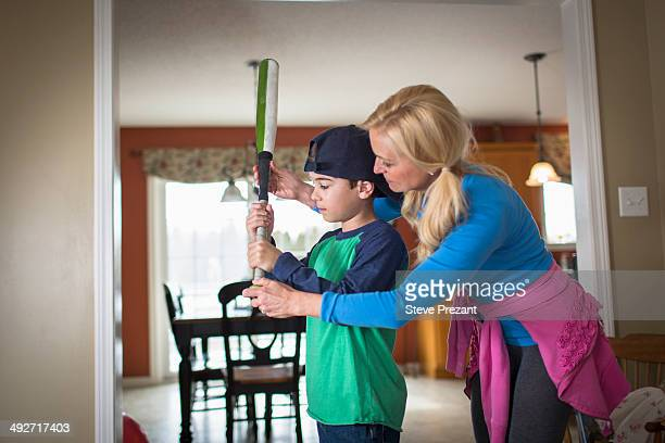 mother teaching son to hold a baseball bat - baseball mom stock pictures, royalty-free photos & images