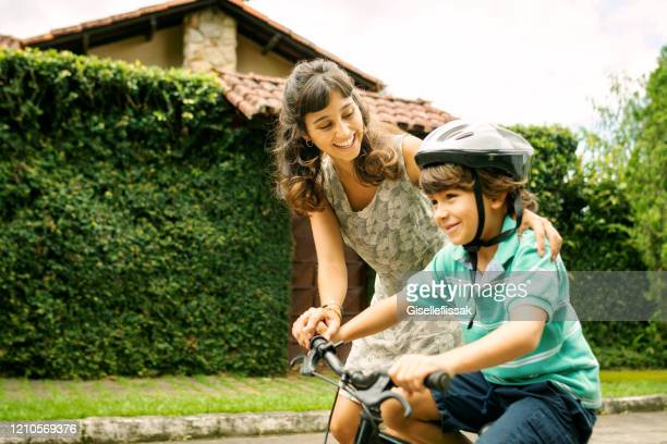 mother teaching son to ride a bike on the street - family with one child stock pictures, royalty-free photos & images