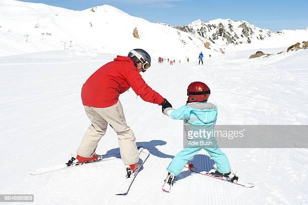 Mother teaching son to ski, rear view