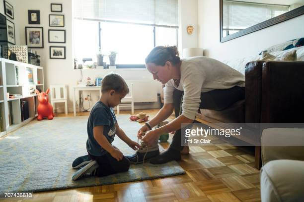 Mother teaching son to tie shoelace