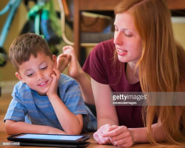 Mother teaching son using digital tablet.