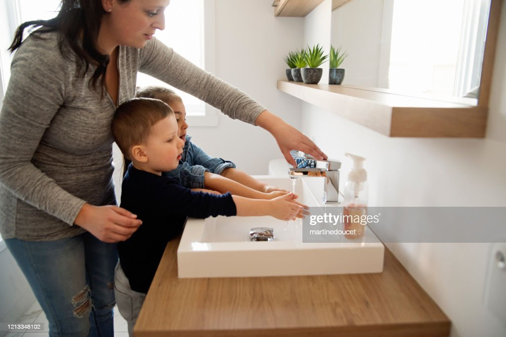 Mother teaching young children how to wash their hands in quarantine isolation Covid-19 : Stock Photo