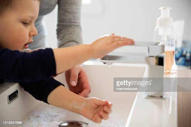 """mother teaching young son how to wash his hands in quarantine isolation covid-19 - """"martine doucet"""" or martinedoucet stock pictures, royalty-free photos & images"""