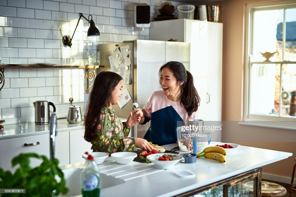 Mother teasing daughter in kitchen whilst making smoothies : Stock Photo