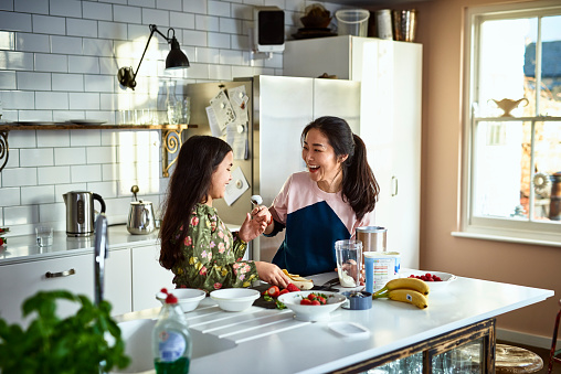 Mother teasing daughter in kitchen whilst making smoothies - gettyimageskorea
