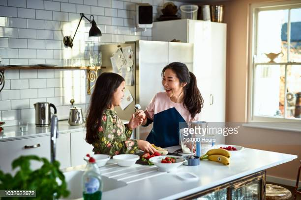 mother teasing daughter in kitchen whilst making smoothies - pre adolescent child stock pictures, royalty-free photos & images