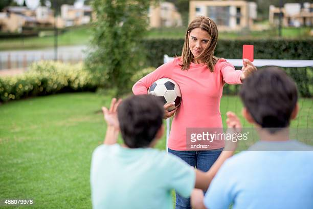 mother telling off her sons while playing football - female umpire stockfoto's en -beelden