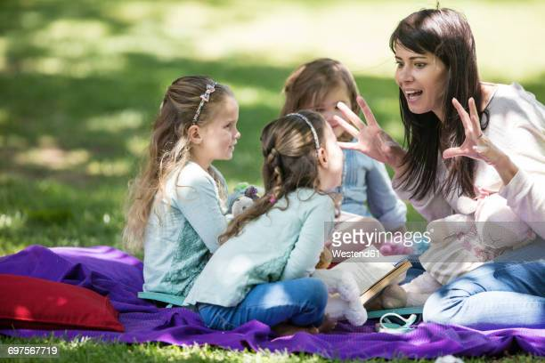 mother telling stories to children on picnic blanket - contar histórias imagens e fotografias de stock