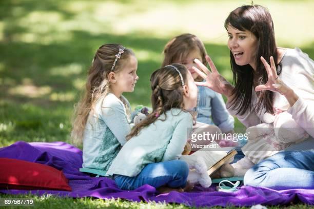 mother telling stories to children on picnic blanket - narração de histórias - fotografias e filmes do acervo