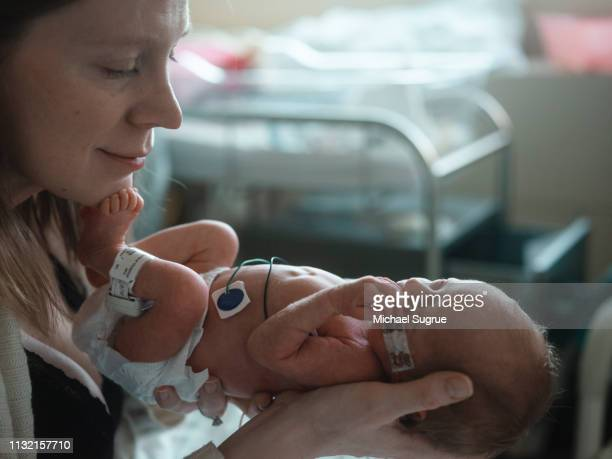 A mother tenderly holds her newborn baby at the hospital.
