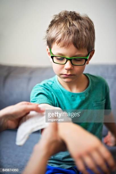 mother tending to her son's wounded arm - wounded stock pictures, royalty-free photos & images