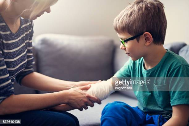 mother tending to her son's wounded arm - wounded stock photos and pictures