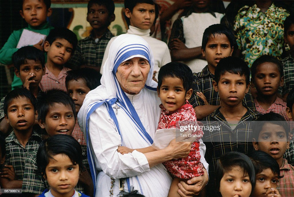 Mother Teresa accompanied by children at her mission in Calcutta, India.