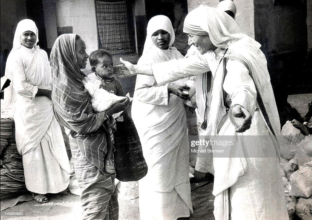 Mother Teresa of Calcutta (1910 - 1997), Head of the Sisters of Charity, working with some of the lepers in Calcutta, 7th December 1971. These are some of the first pictures taken of her after she was highlighted in a BBC documentary film showing her work with the poor and underprivileged of Calcutta. She is seen handing out Christmas gifts in a leper colony - the gifts are a bag of rice and a blanket.