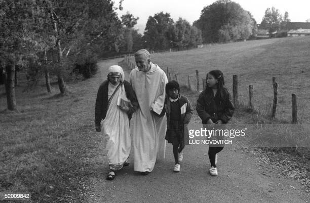 Mother Teresa of Calcutta the humble nun known as the 'saint of the gutters' walks together with the brother Roger SchutzMarsauche founder and...