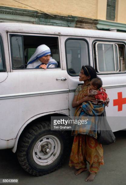 Mother Teresa talking with a poor woman and her child from a Red Cross minibus in Calcutta India