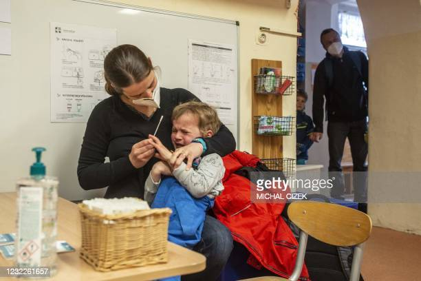 Mother tests her child on Covid-19 at a kindergarten on April 12, 2021 in Prague as kindergartens and primary schools re-opened as some restrictions...