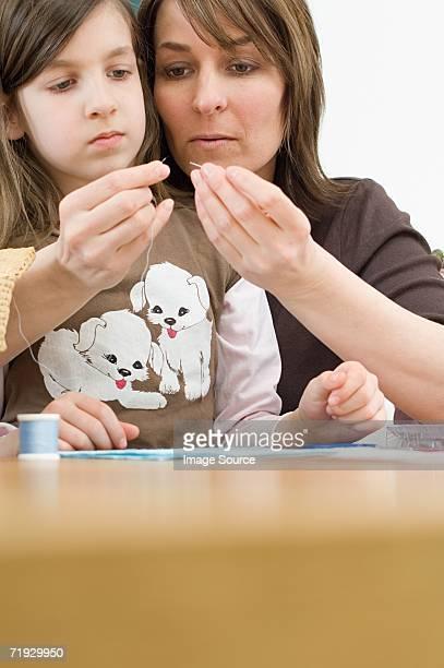 Une mère enfiler une aiguille