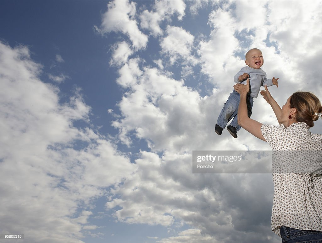 mother throwing boy in the sky : Stock Photo