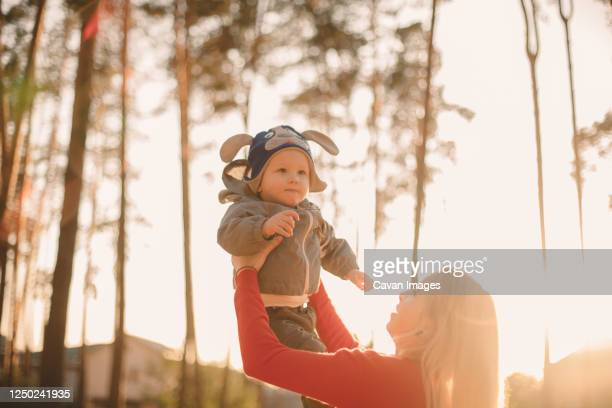 mother throwing son in air while playing in park during sunny day - ukraine stock pictures, royalty-free photos & images