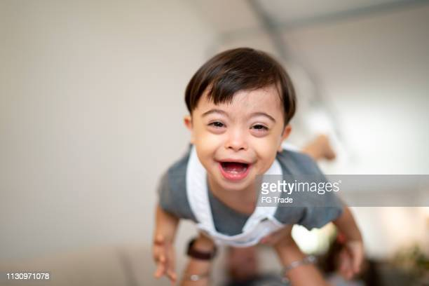 mother throwing up her son with down syndrome at home - down syndrome stock pictures, royalty-free photos & images