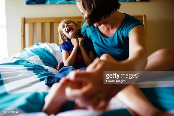 mother tickling daughters feet while sitting on bed - kitzeln stock-fotos und bilder
