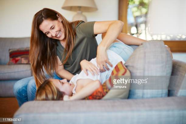 mother tickling her daughter in the living room. - family at home stock pictures, royalty-free photos & images