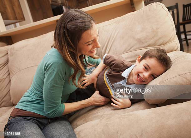 Mother tickling her son (6-7) on couch