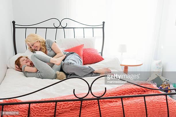 Mutter kitzeln kleines Mädchen in Startseite Schlafzimmer liegen in den Morgen.