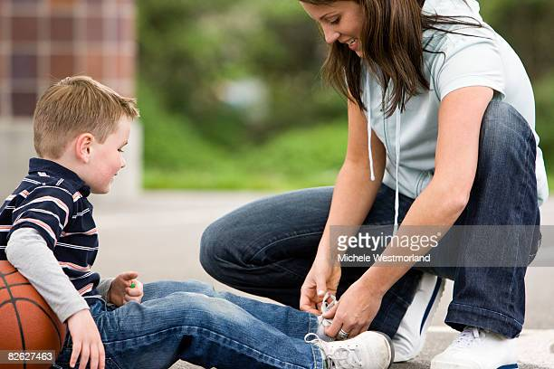 mother ties son's shoe - basketball shoe stock photos and pictures