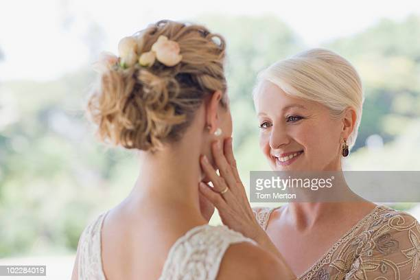 Mother touching brides face