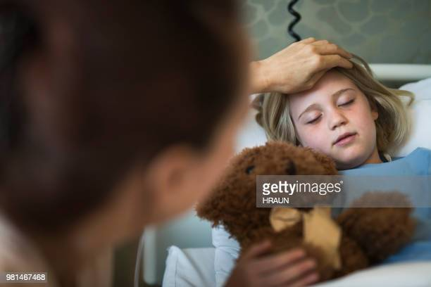 Mother touching sick patient's forehead