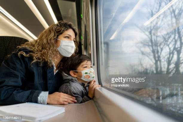 mother traveling by train with her son during the pandemic wearing facemasks - biosecurity stock pictures, royalty-free photos & images