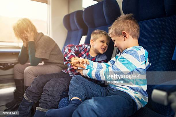 Mother travelling on train with naughty kids