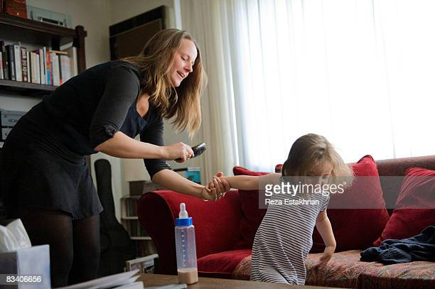 mother tries to brush playful daughter's hair - naughty america stock pictures, royalty-free photos & images