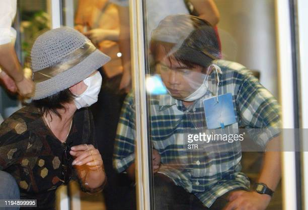 Mother tries to communicate through a glass wall with her son, a Vietnamese student who has just flew back from China and is placed in quarantine in...