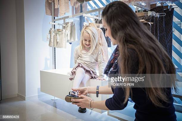 Mother trying shoes on young daughter in childrens clothes shop
